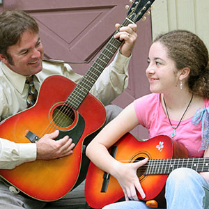 padre e figlia a suonare la chitarra