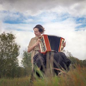 una donna impara a suonare la fisarmonica sull'erba